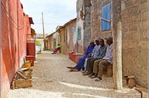 Village street with men sitting on bench