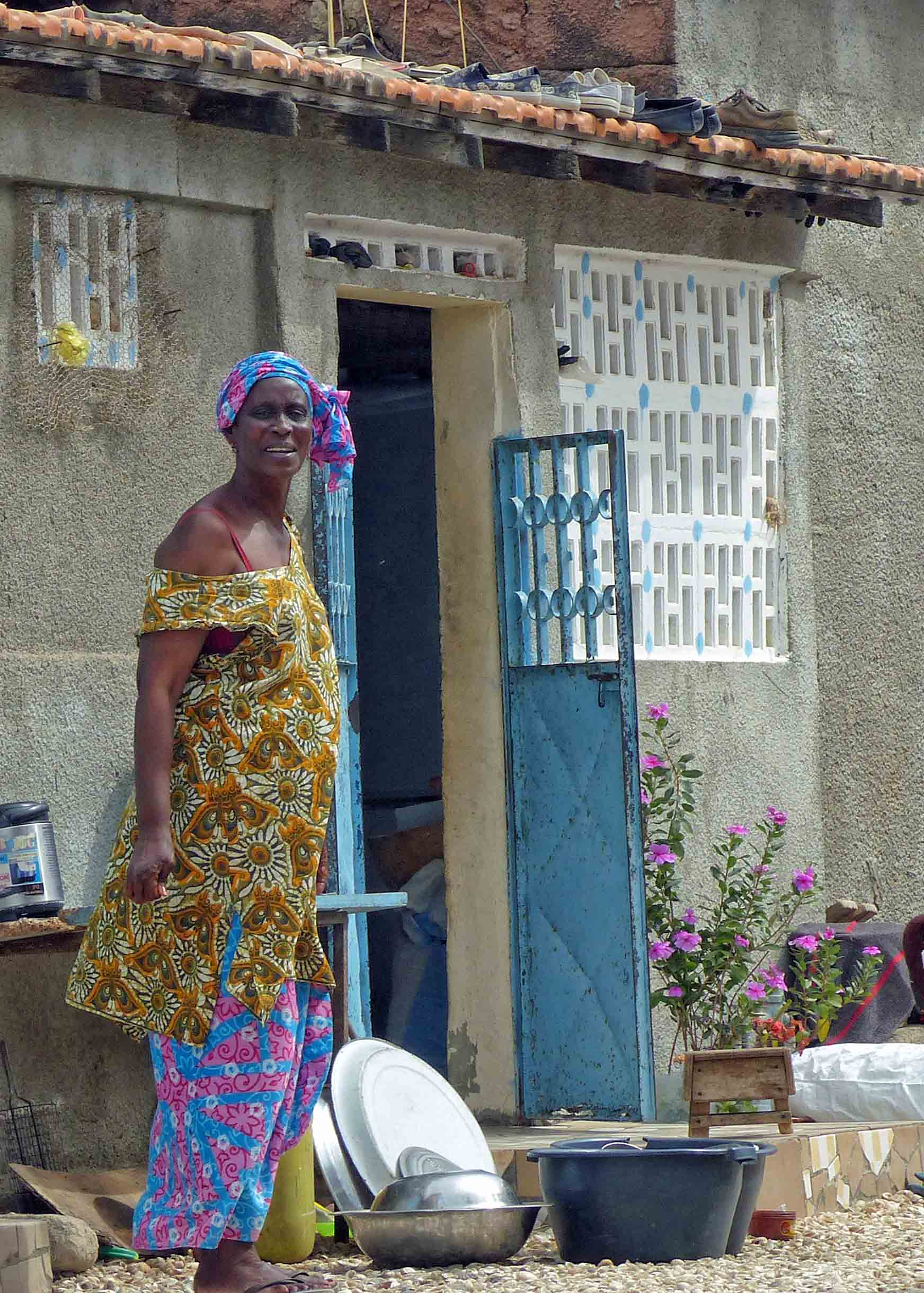 Lady in African dress outside her house