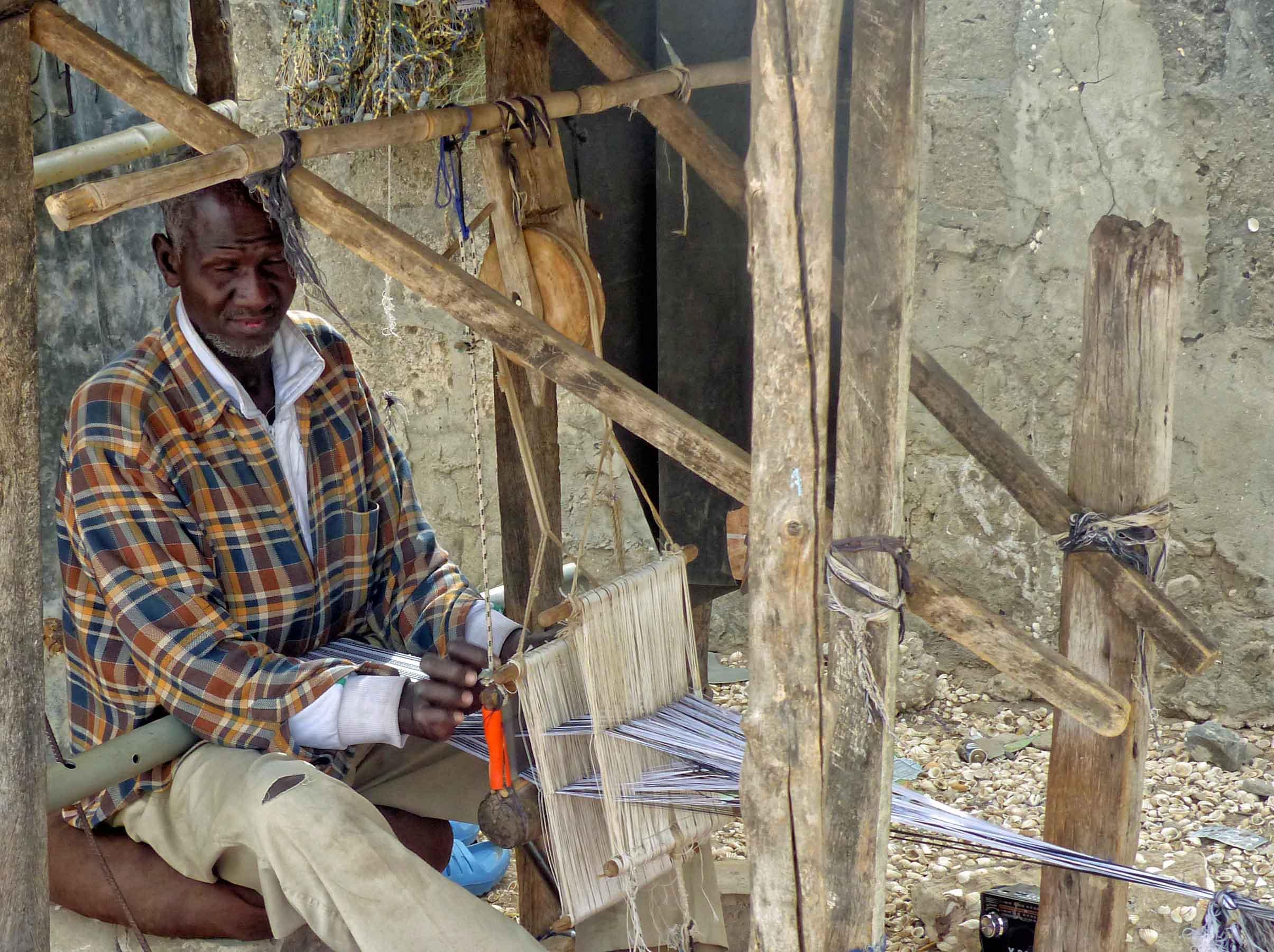Man weaving on simple loom