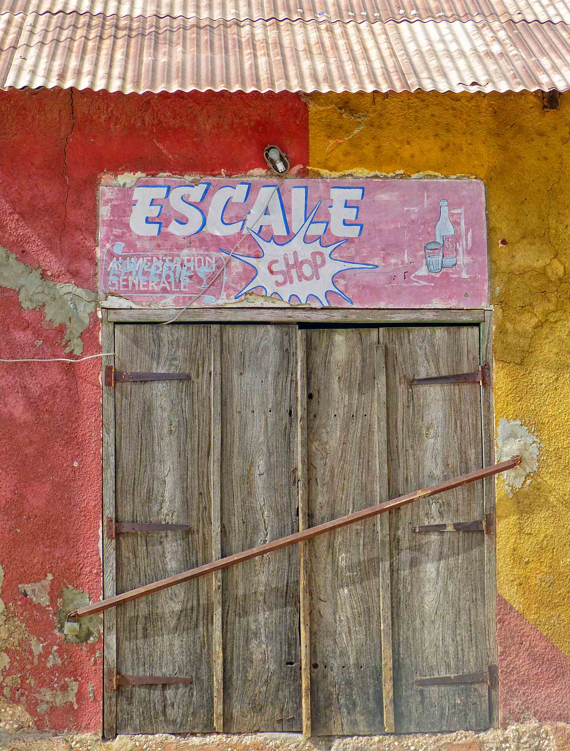 Closed wooden doors on colourful building with tin roof