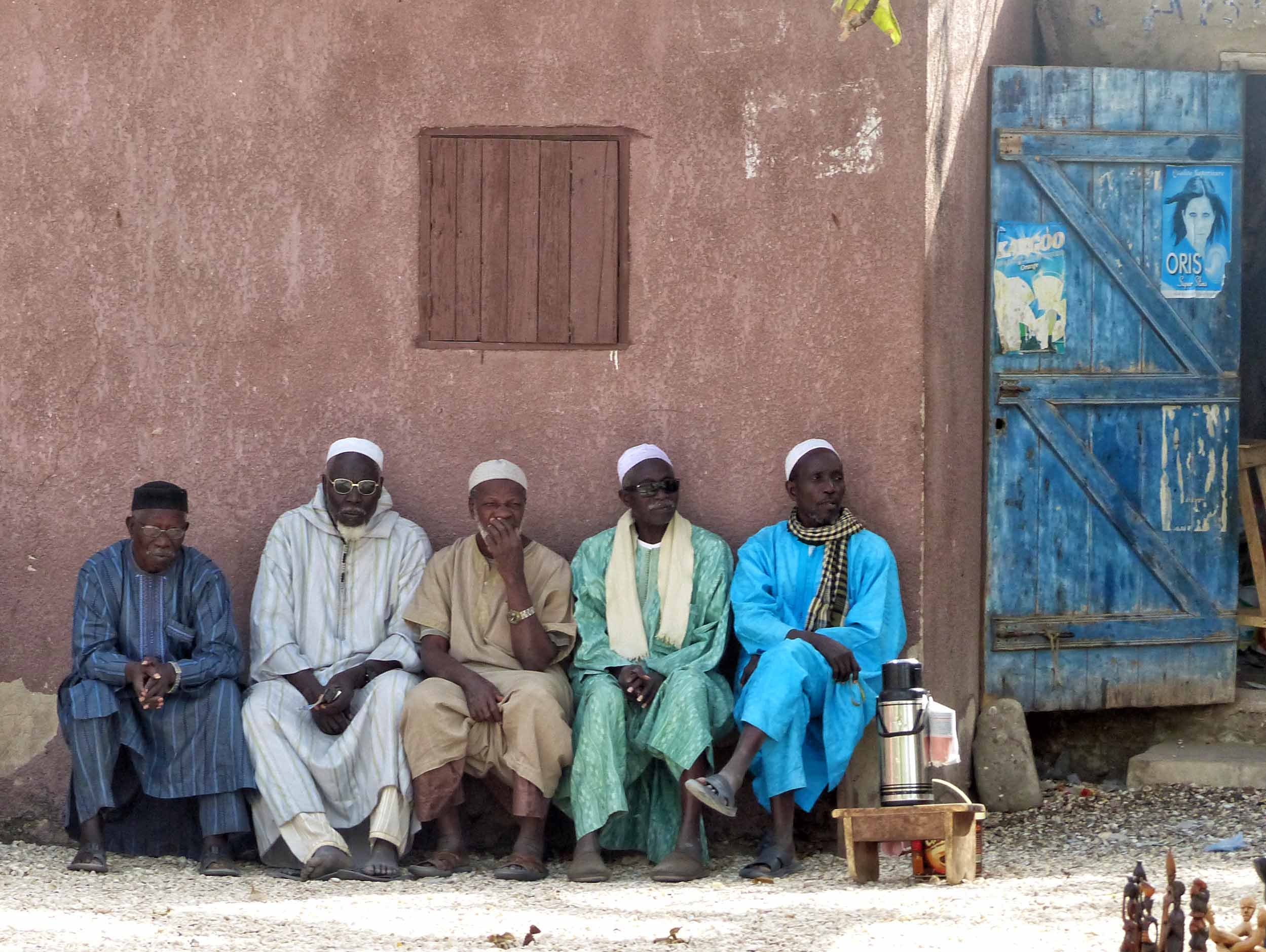 Five men in African dress sitting on a bench