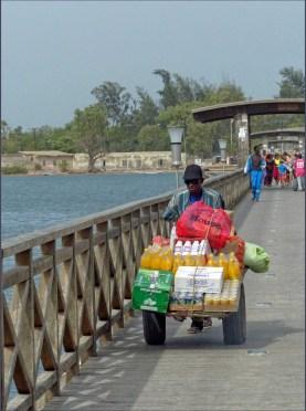 Man wheeling trolley on wooden bridge