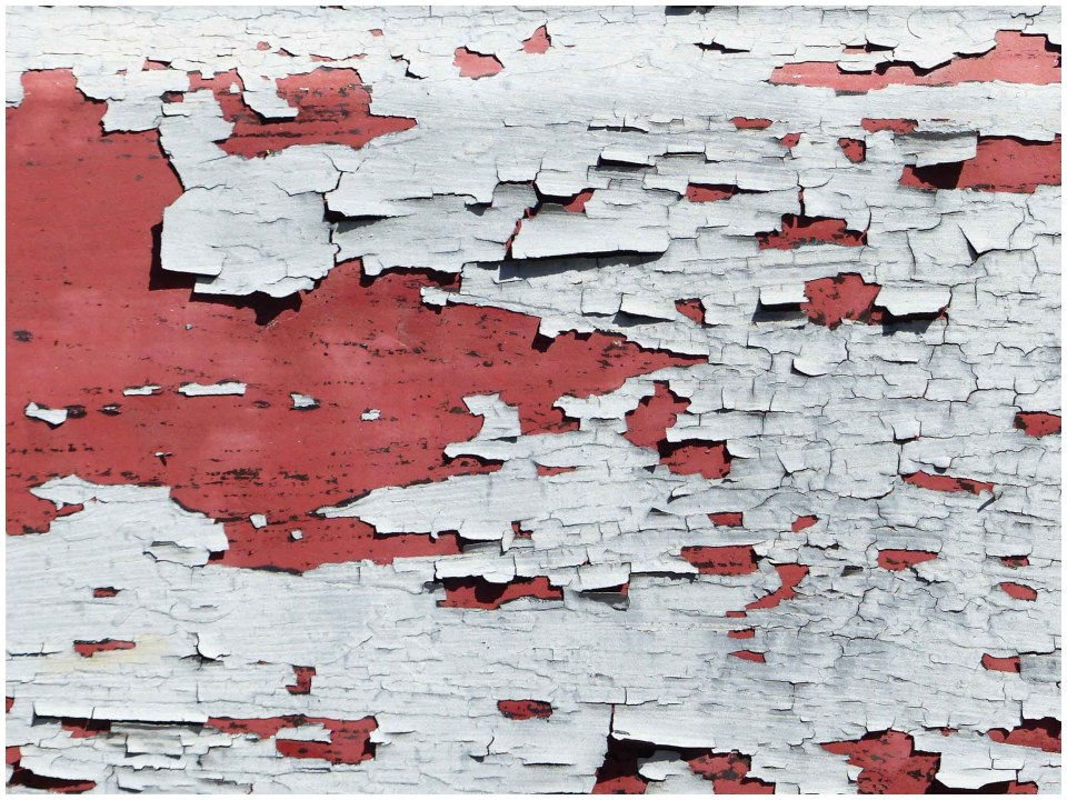 White paint flaking off red background