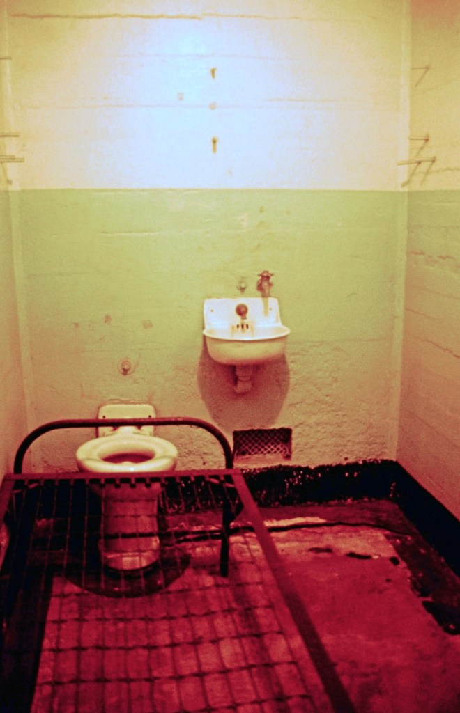 Prison cell with metal frame bed and toilet