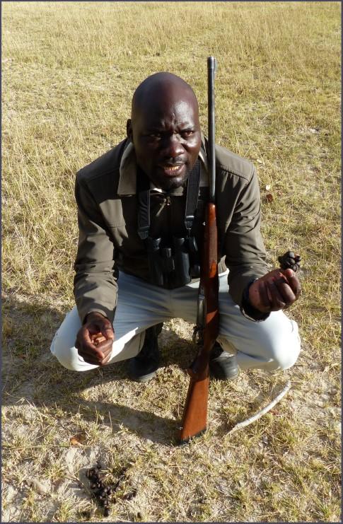 Man with rifle and animal dung