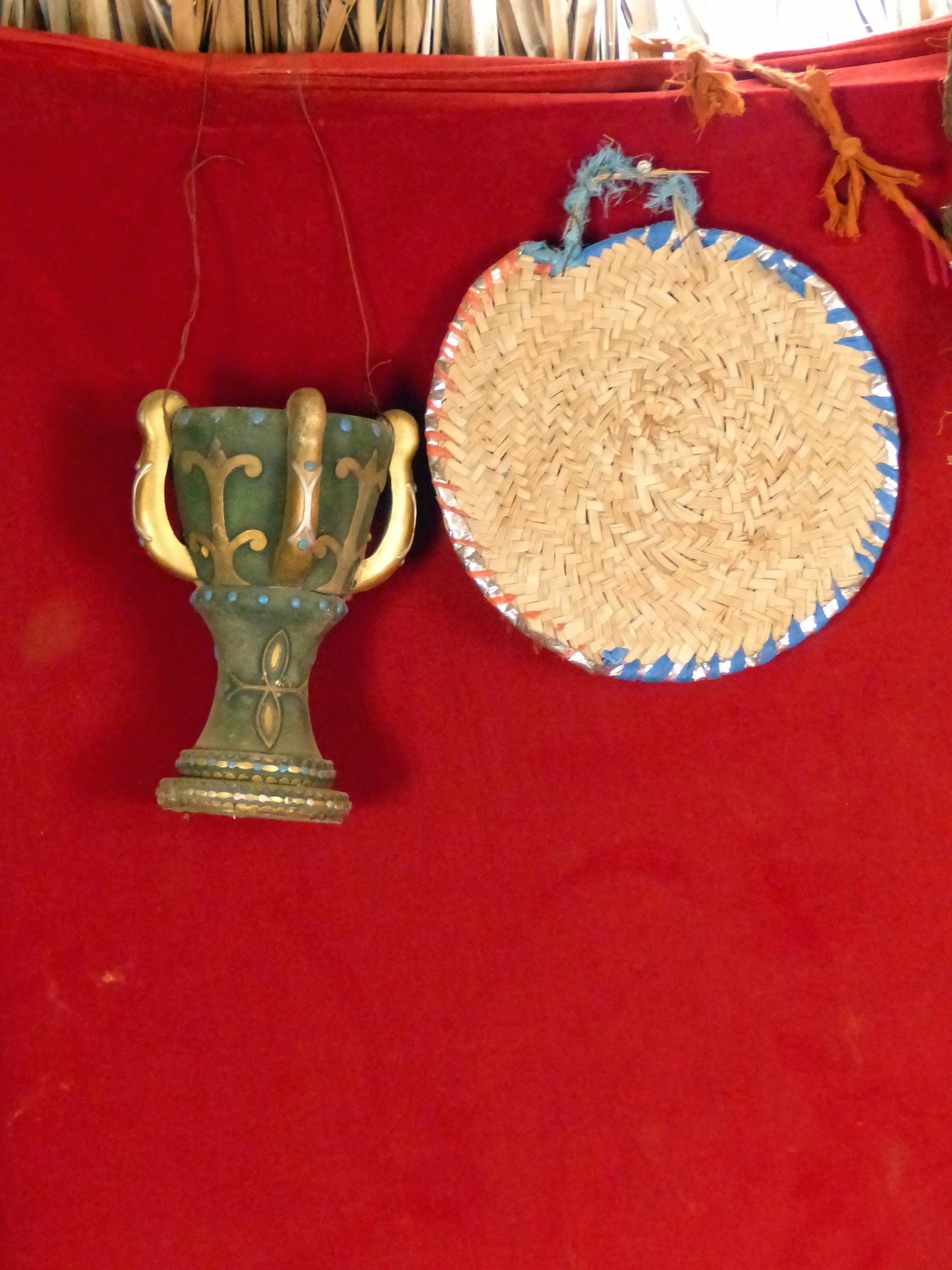 Ornate cup and straw mat hanging on red background