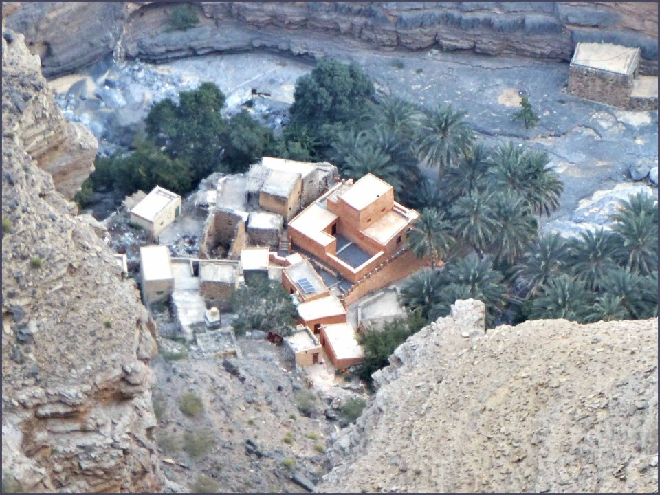 Looking down at flat roofs of a village and palm trees