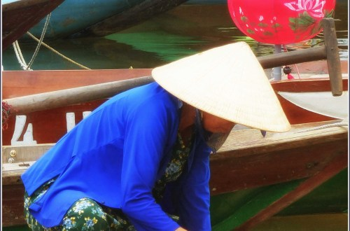 Lady in conical hat on a small boat