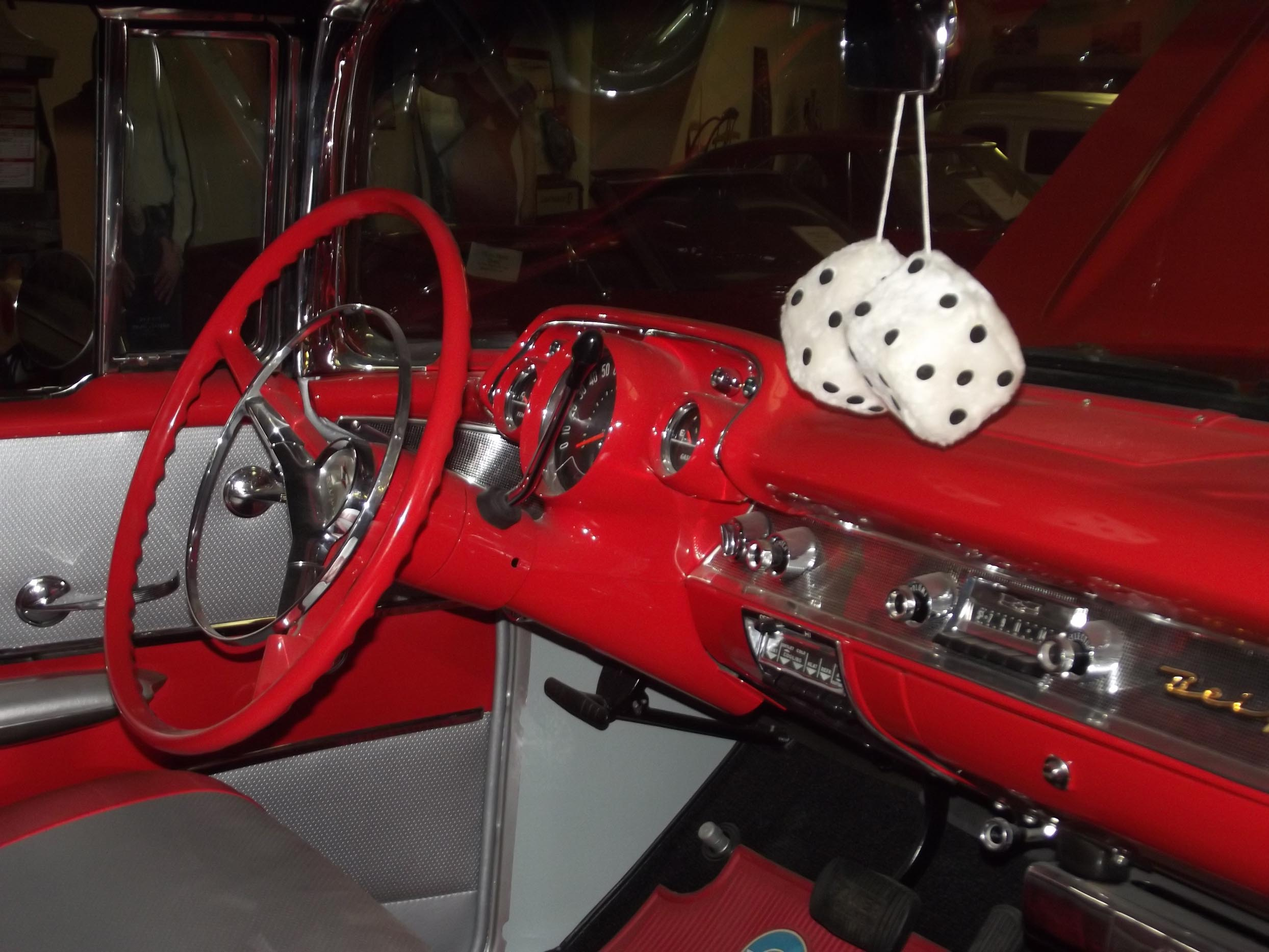 Inside a car with red dashboard and steering wheel