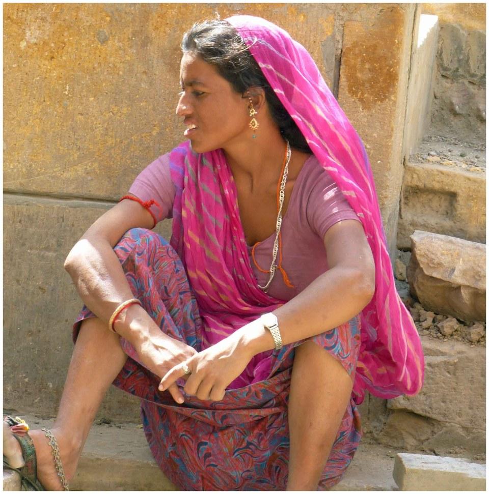 Lady in pink sari sitting on stone step