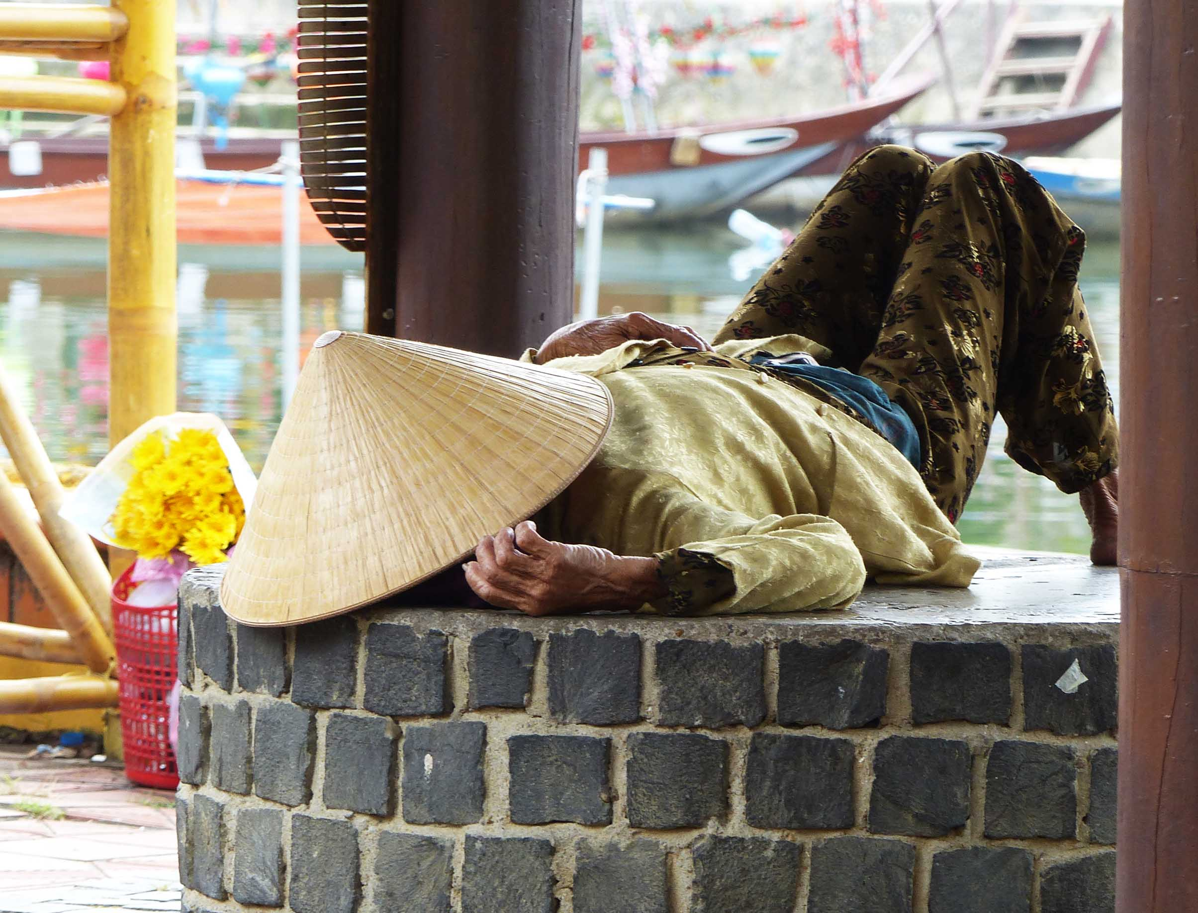 Man lying down with hat over his face