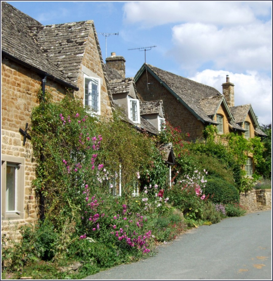 Yellow stone cottages with roses growing around them