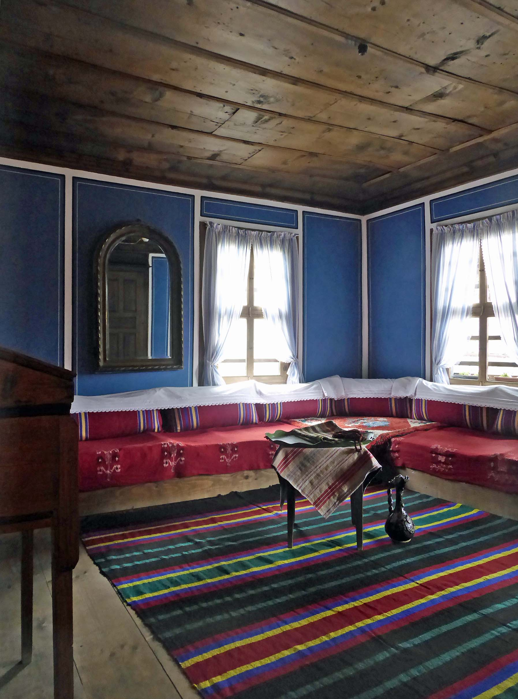 Room with blue walls, striped rug and bench seating