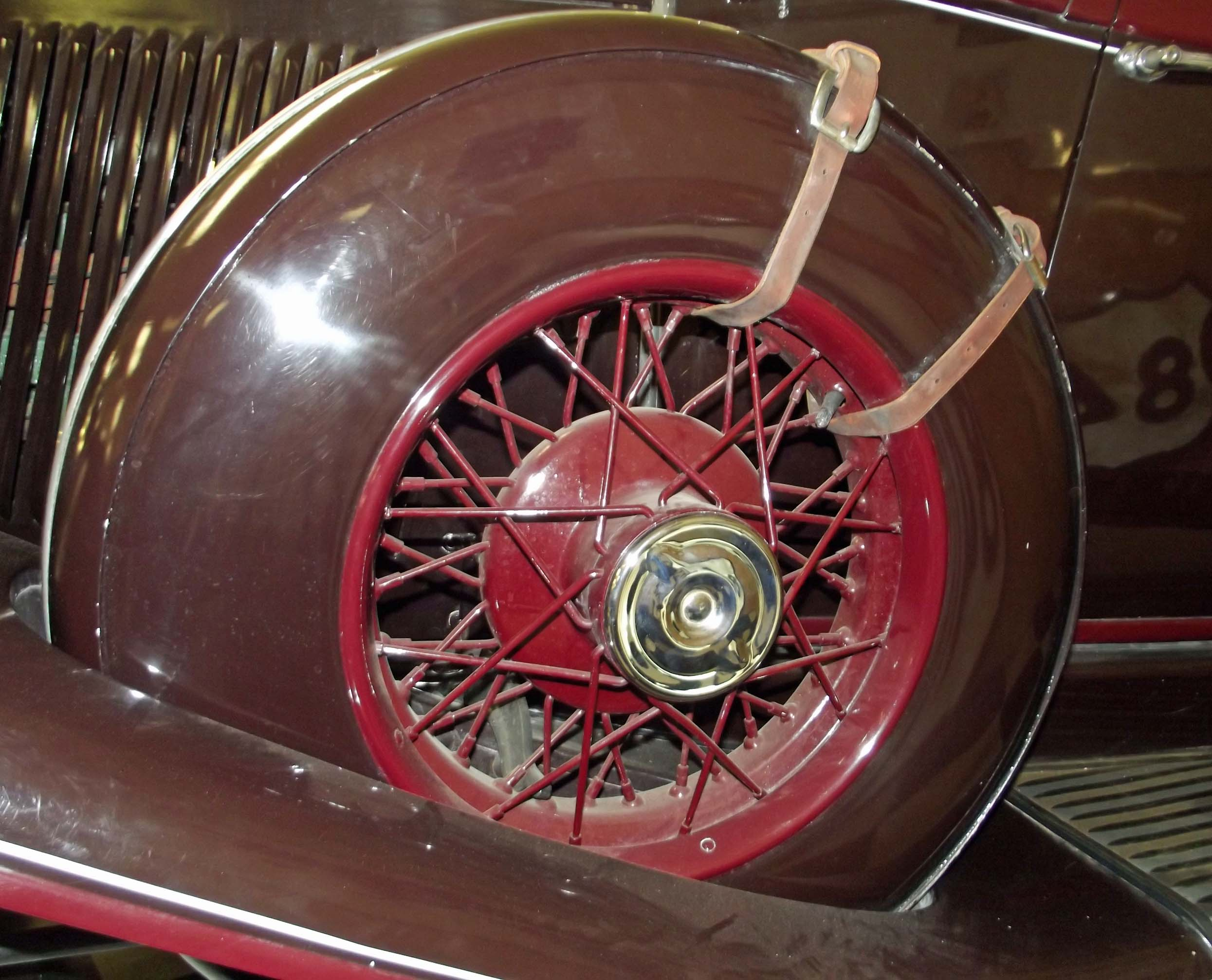 Brown car wheel with red hub spokes