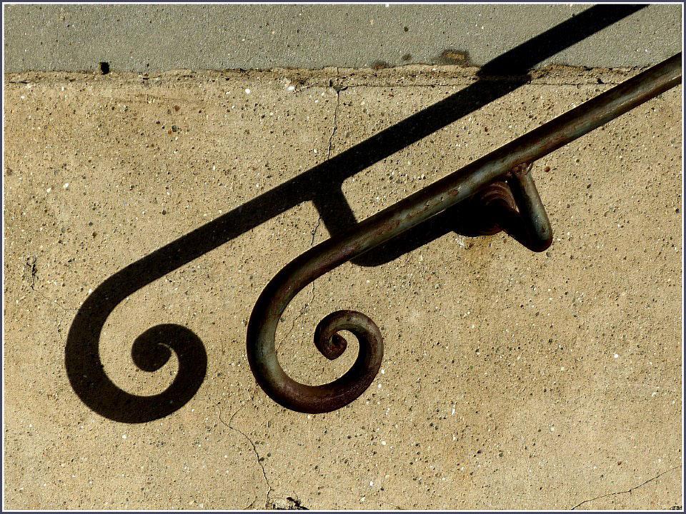 Shadow of worn metal handrail on a wall