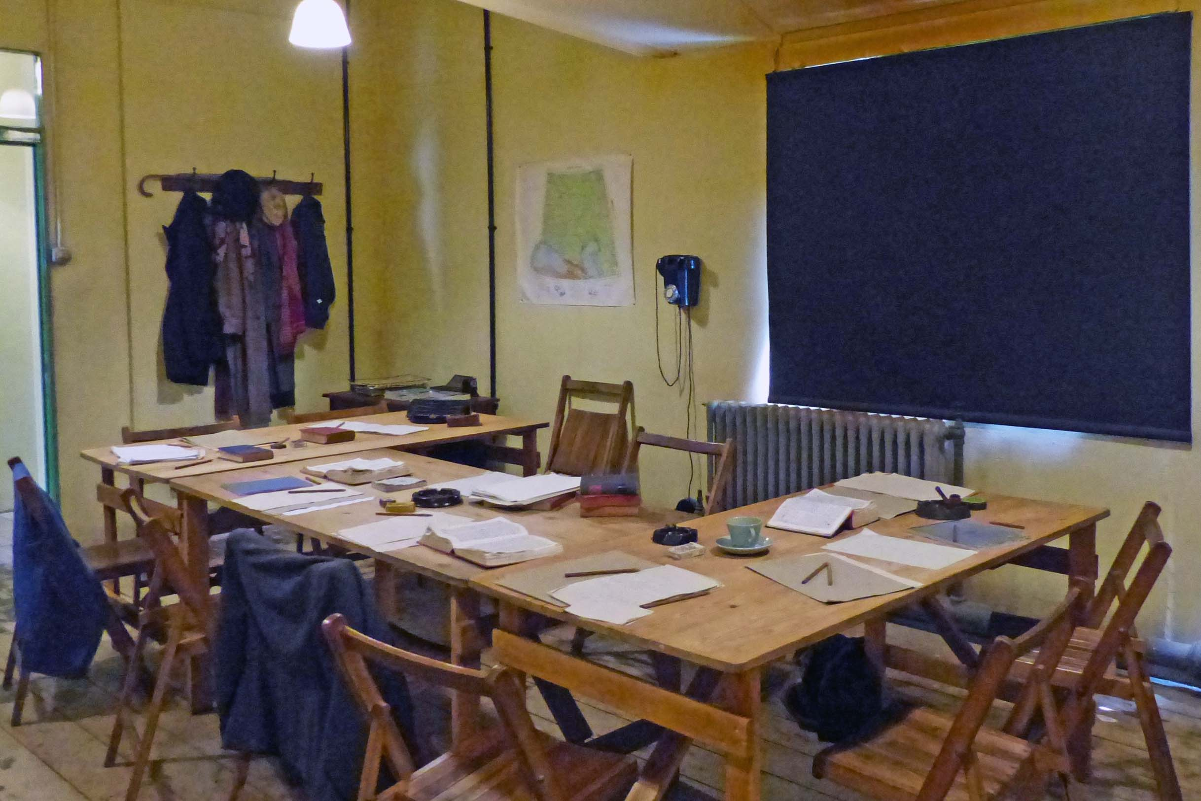 Room with wooden tables and chairs and blackout blind