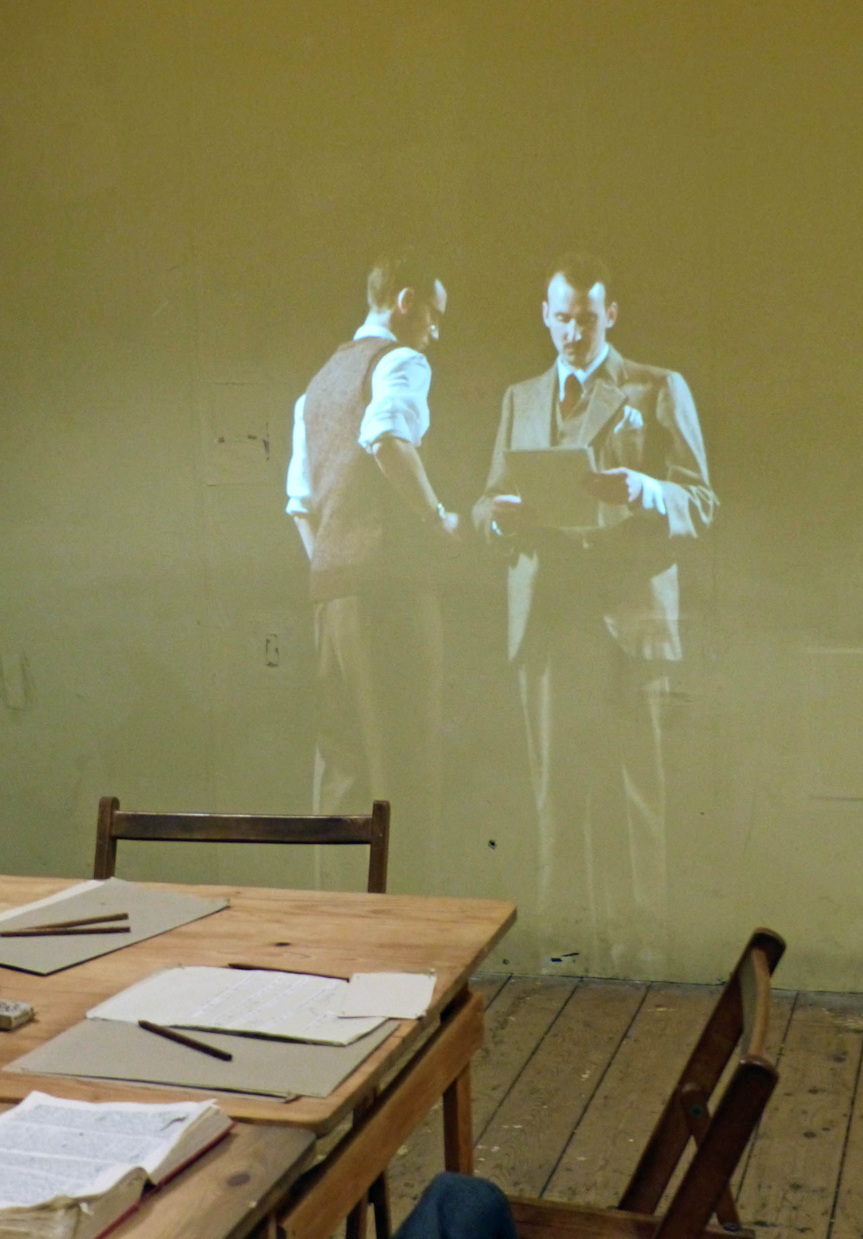 Projection on a wall of two men in 1940s clothing