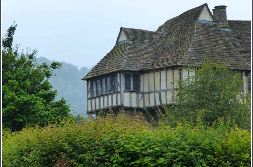 Half-timbered building seen above a hedge