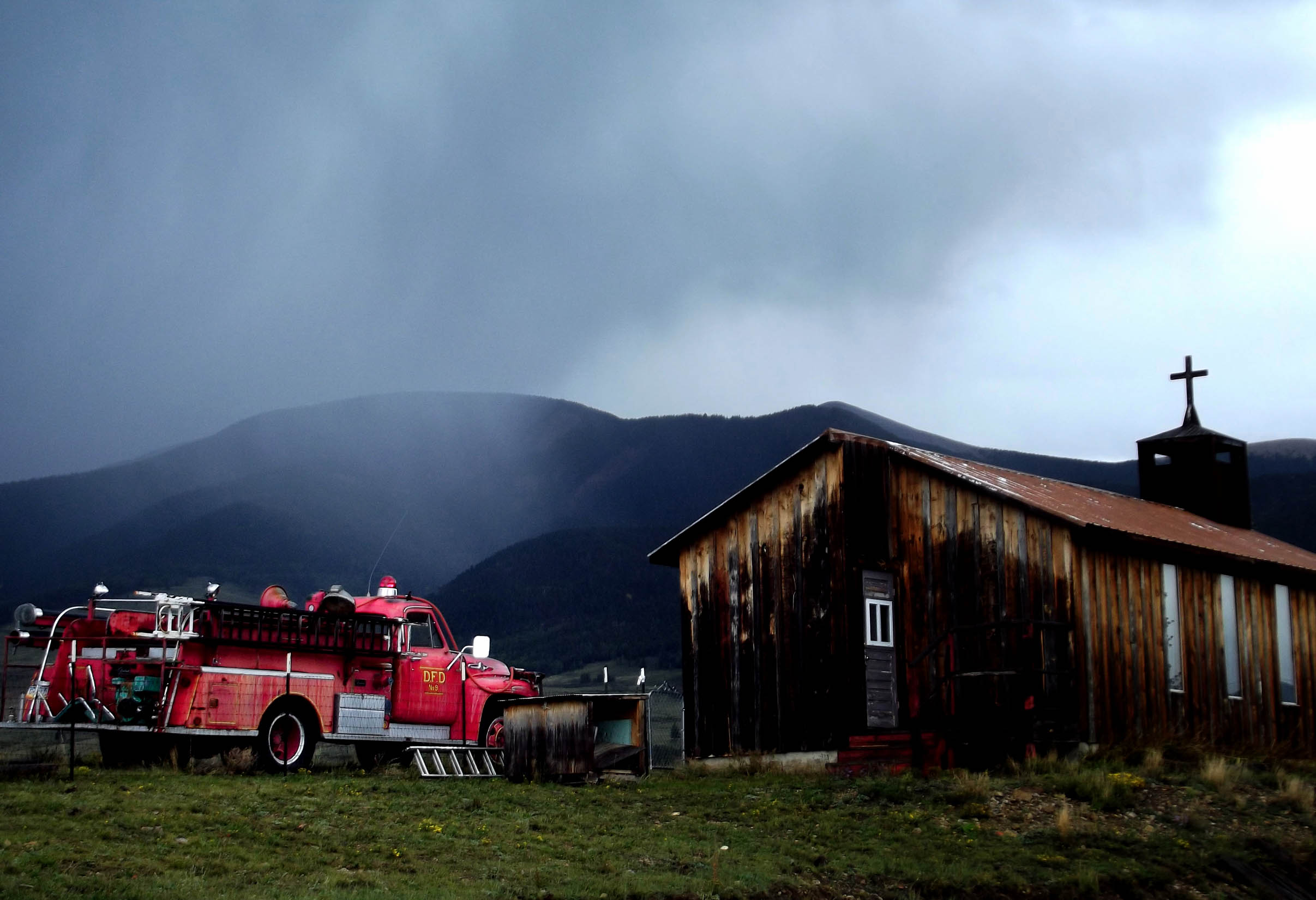 Red fire truck and small wooden church