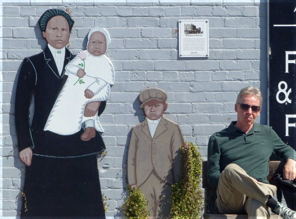 Man sitting by mural of lady with children