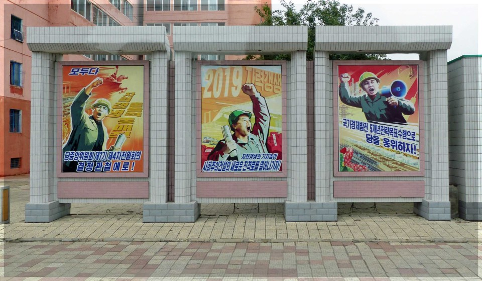 Three large posters depicting men with hard hats, gesticulating
