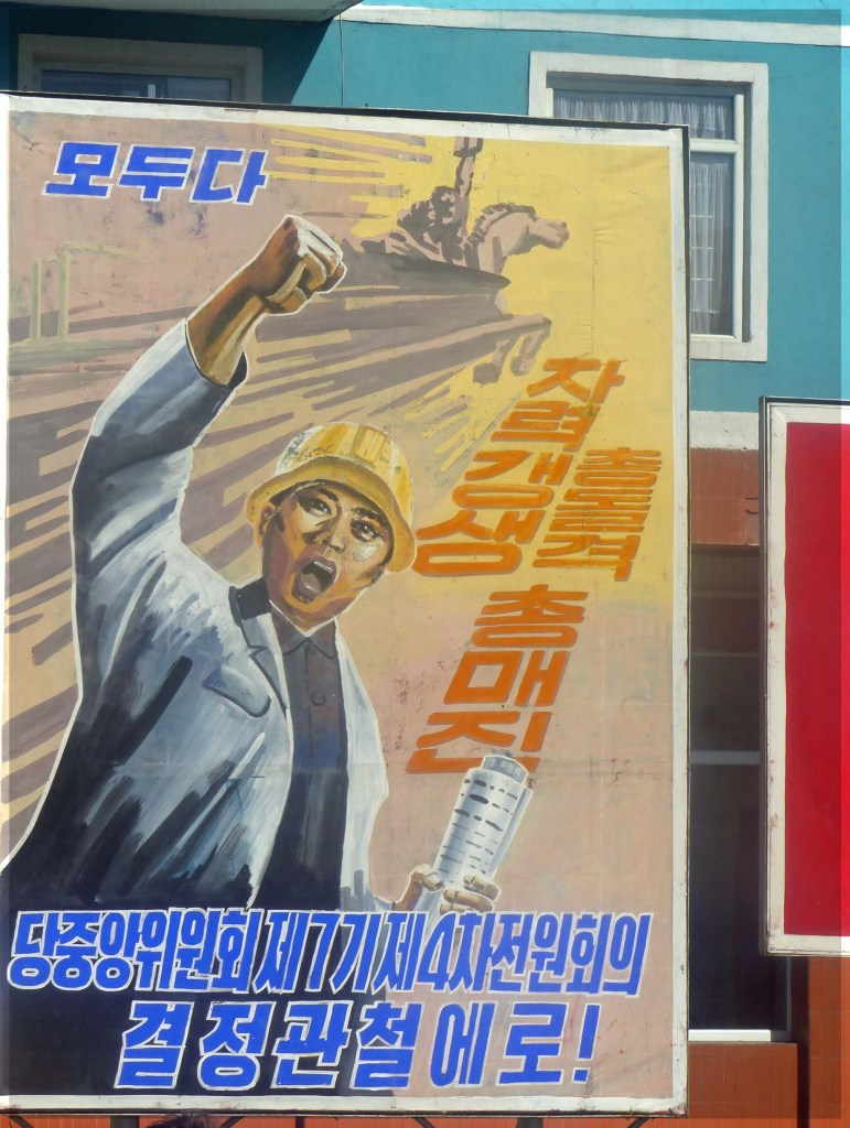 Large poster depicting man in hard hat and slogans