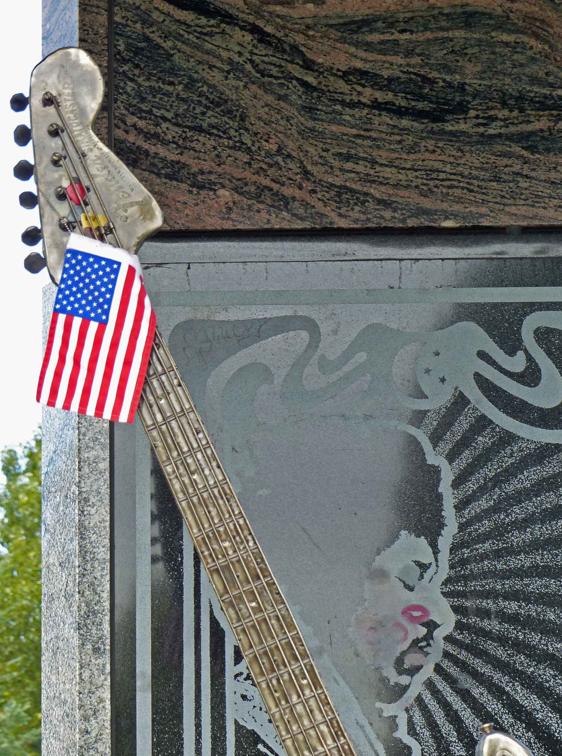 Metal sculpture of a guitar head with small US flag