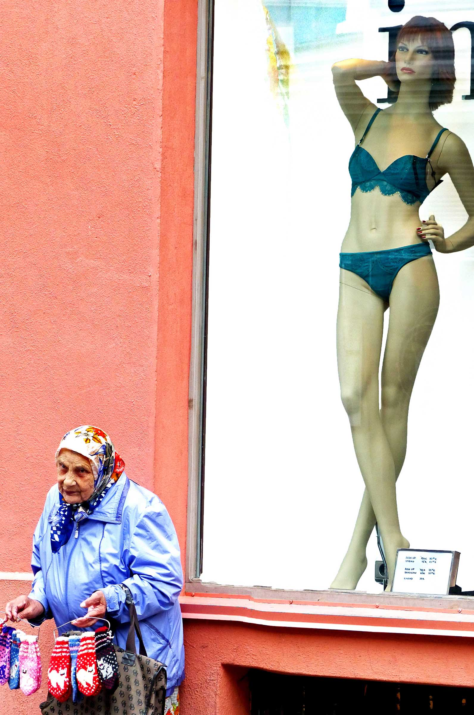 Old lady displaying knitted goods in front of window with manequin modelling underwear