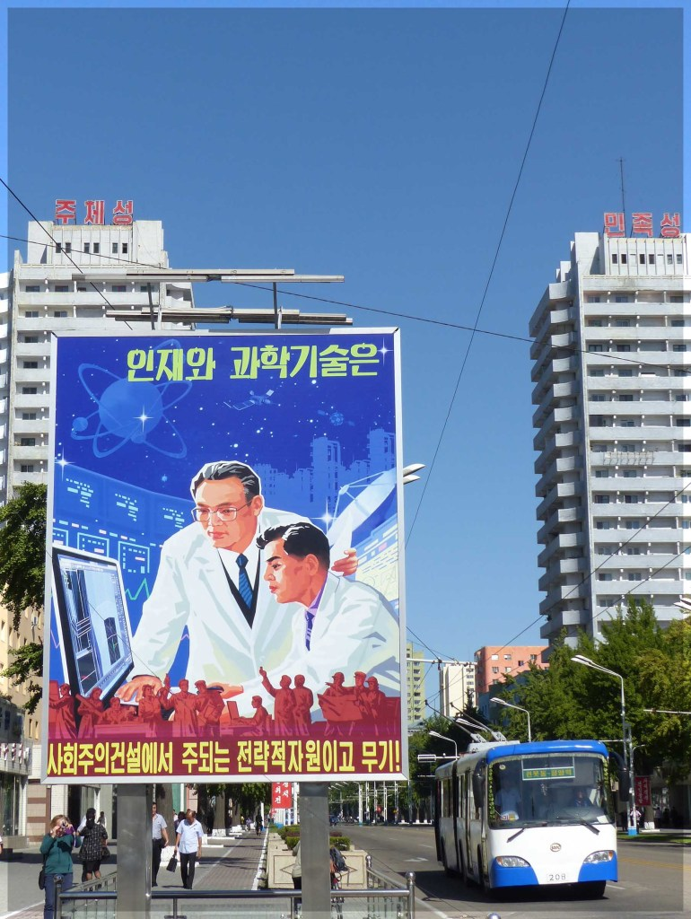 Large poster depicting two men at a computer, with bus passing
