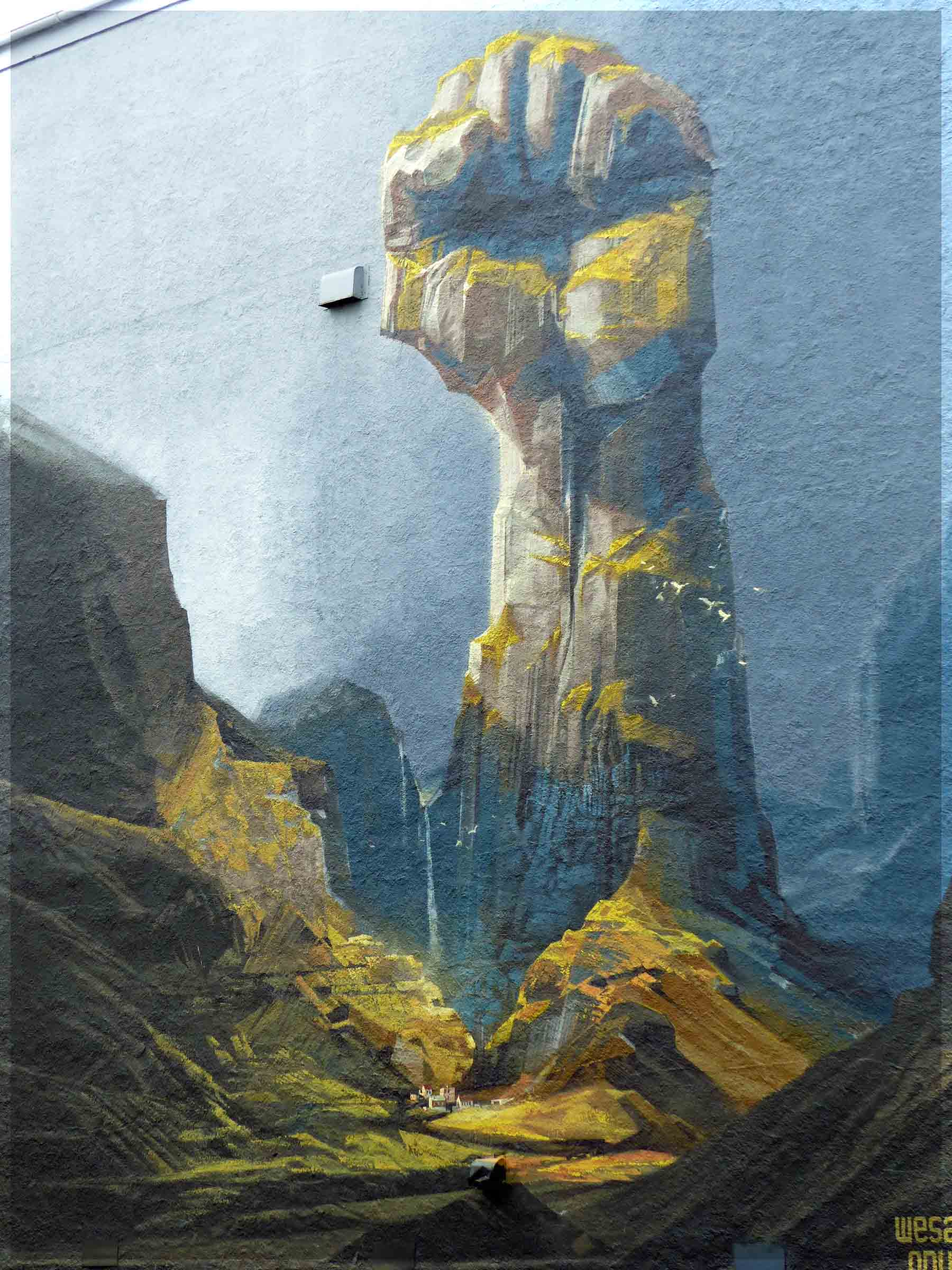 Mural of giant fist emerging from mountainous landscape