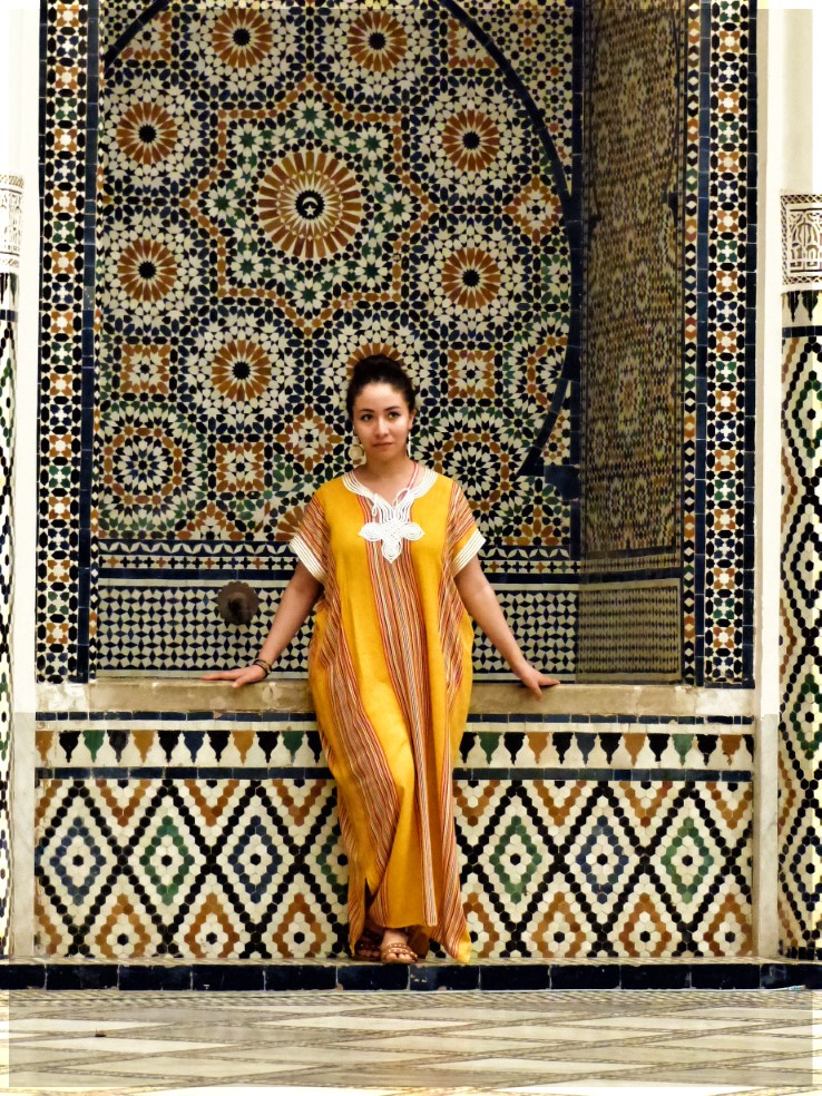 Girl in long yellow robe posing in front of tiled alcove