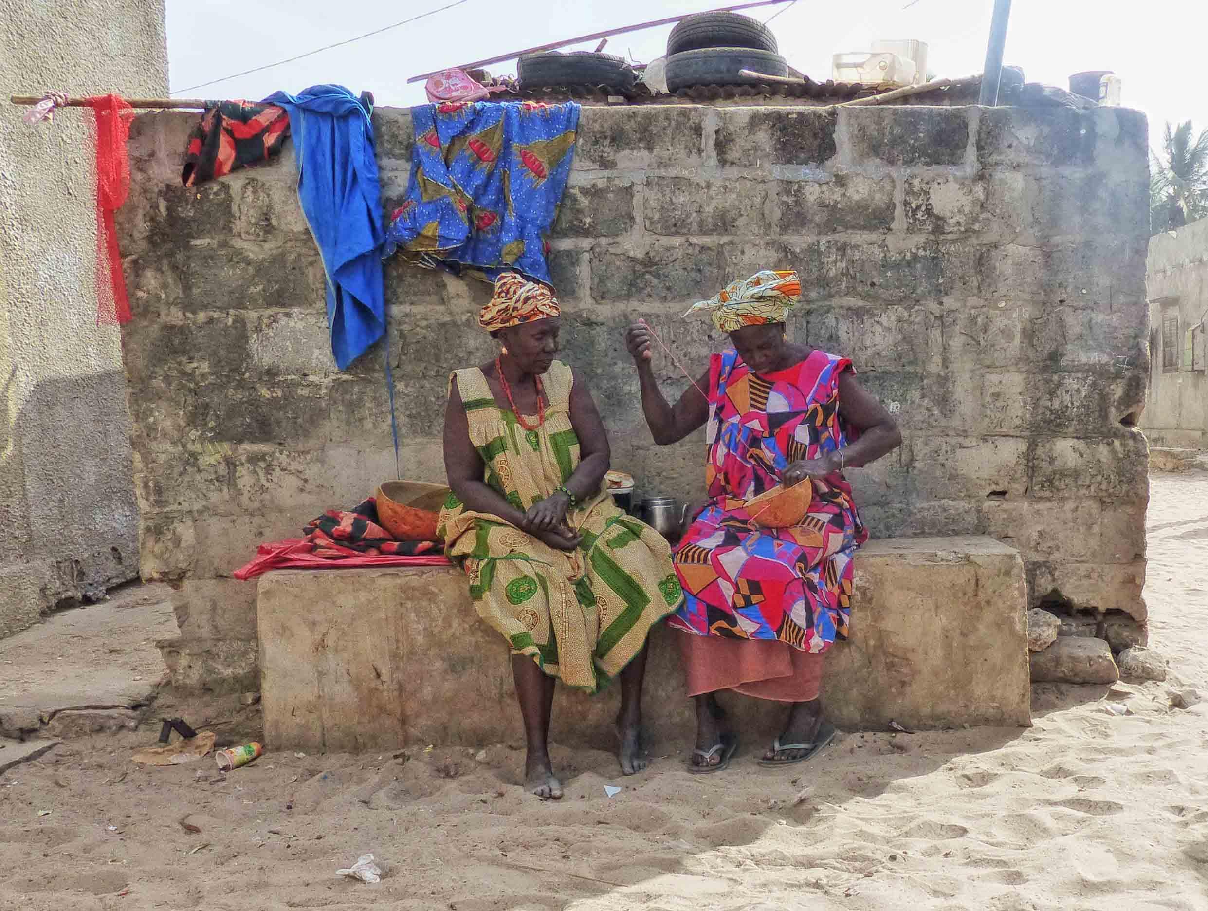 Two women in African dress making baskets