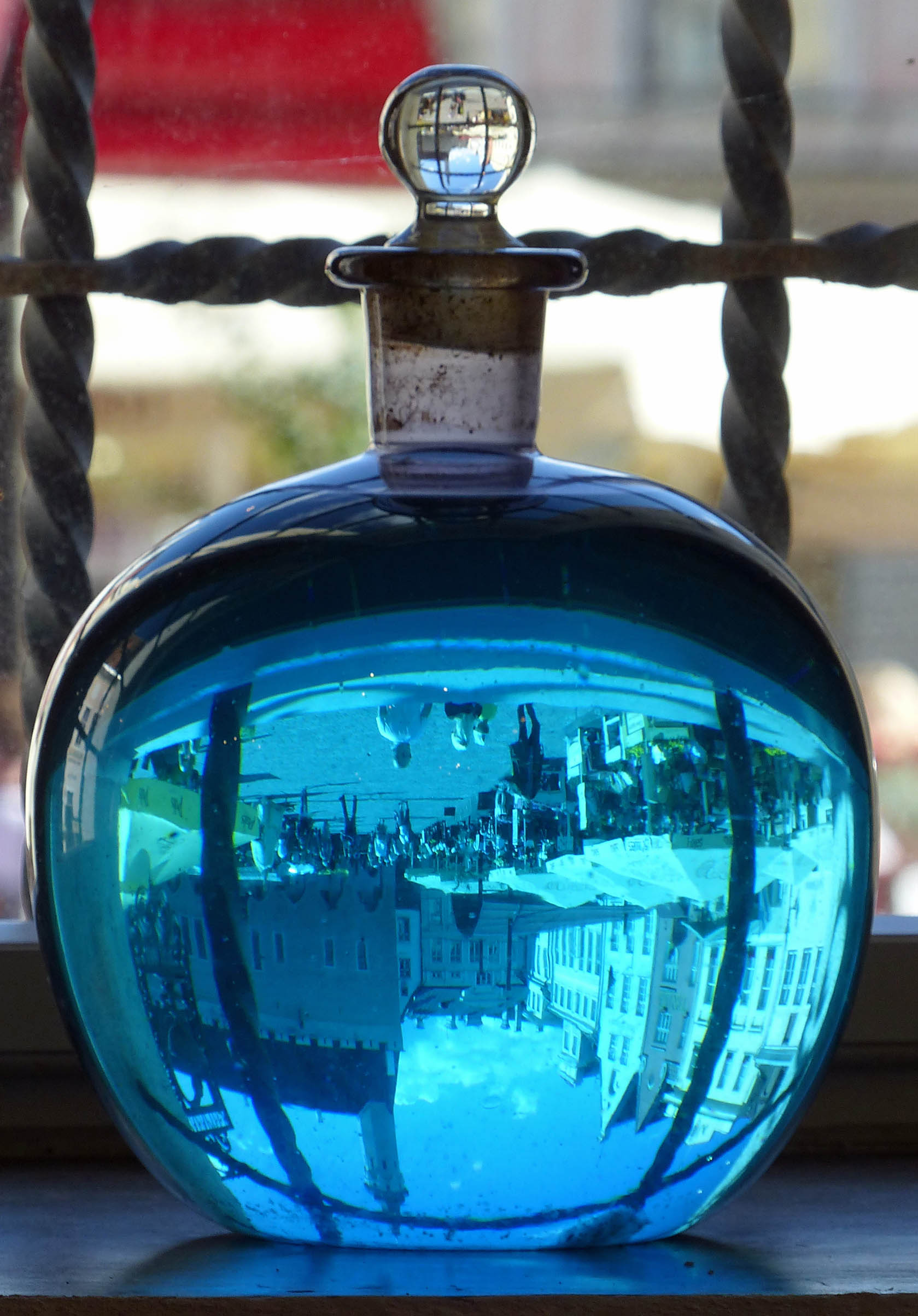 Large bottle of blue liquid in a window with exterior scene refracted upside down