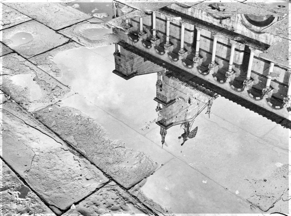 Church reflected upside down in a puddle on cobbled stones