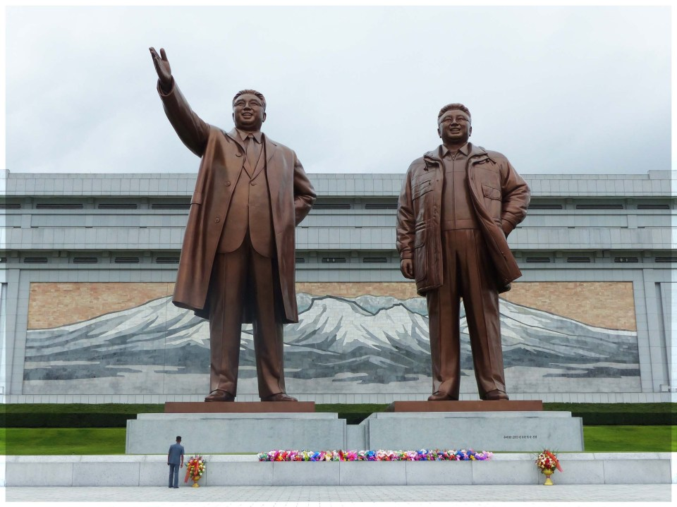 Two huge bronze statues of men with single person in front