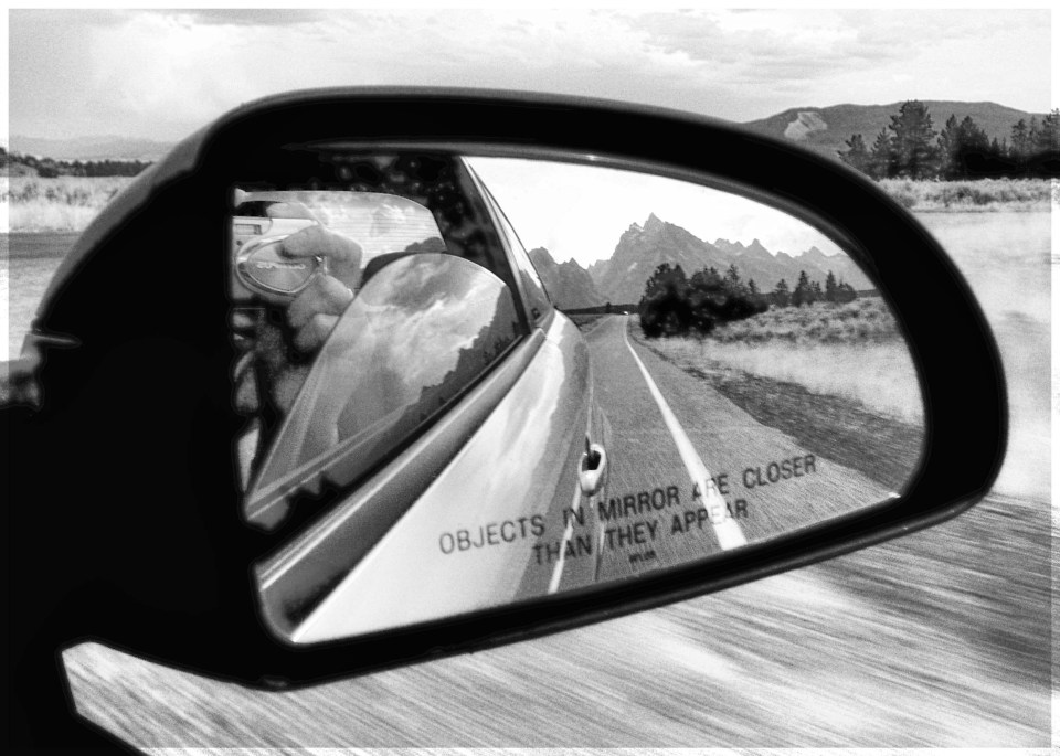 Black and white photo of landscape reflected in car mirror