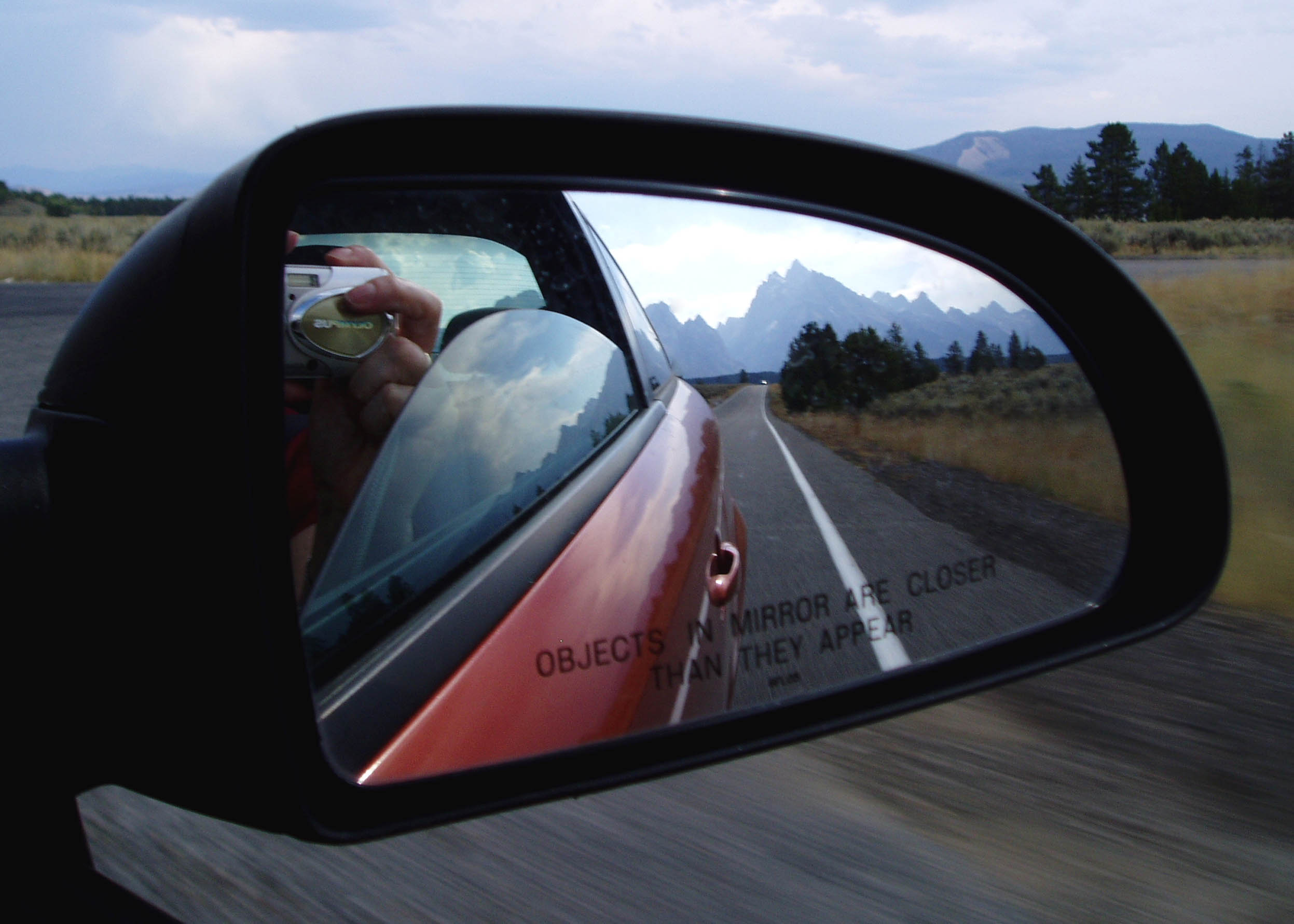Mountain landscape reflected in car mirror