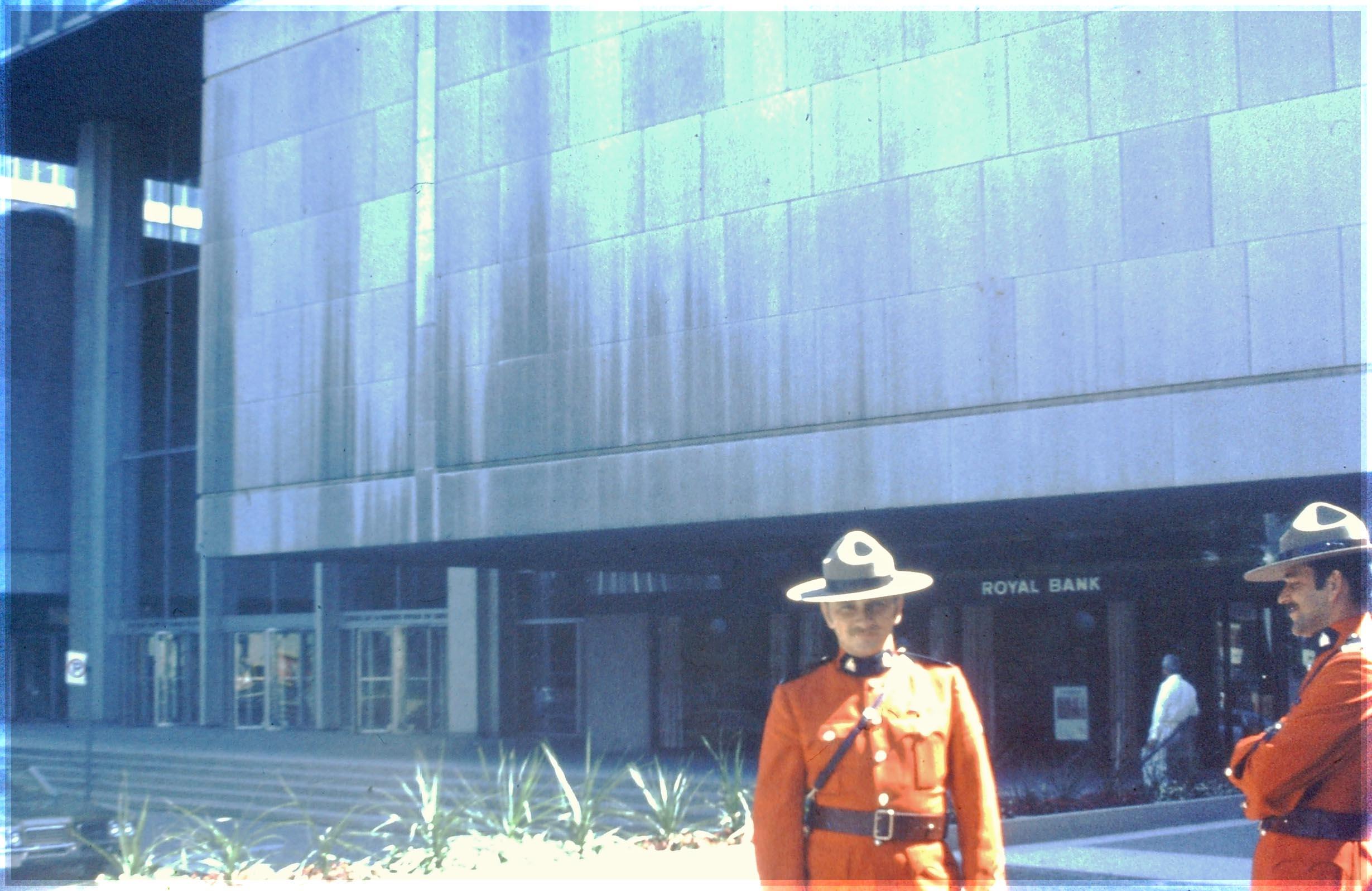 Two men in uniform outside modern building