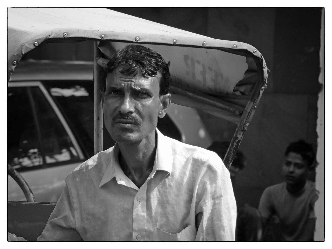 Black and white photo of man with rickshaw