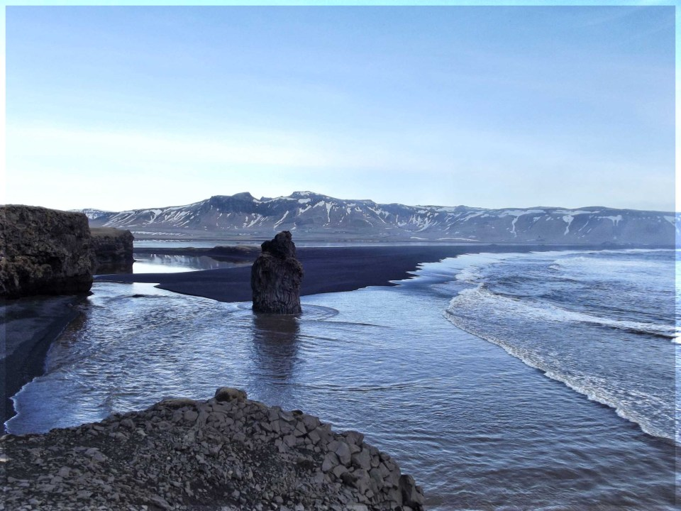 Coastal scenery with black sand, rock stack and mountains