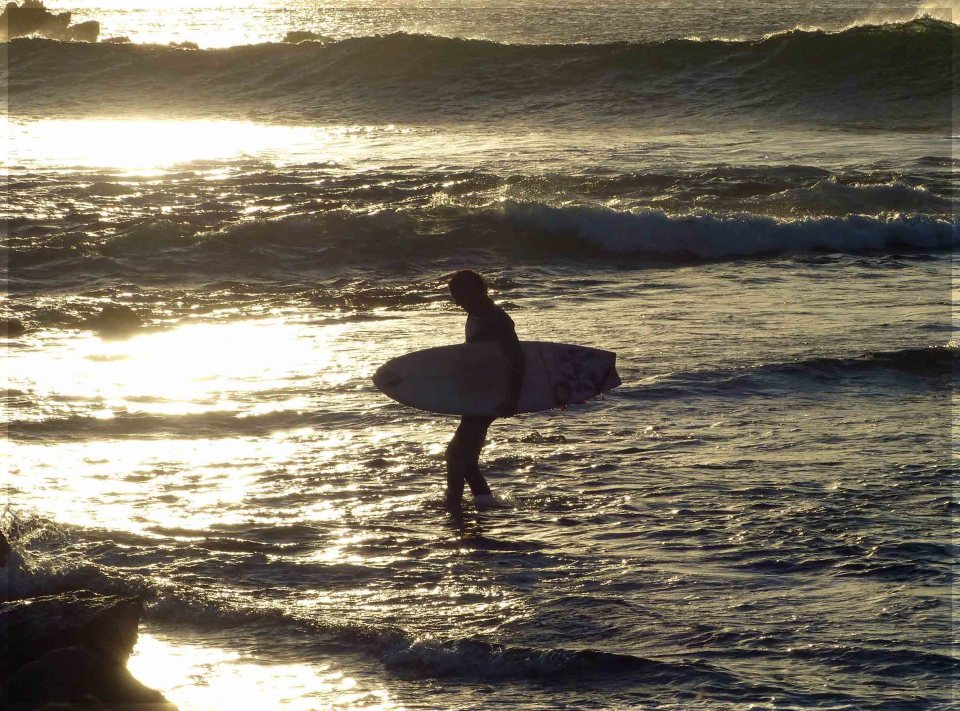 Man carrying surfboard with sea reflecting sunlight
