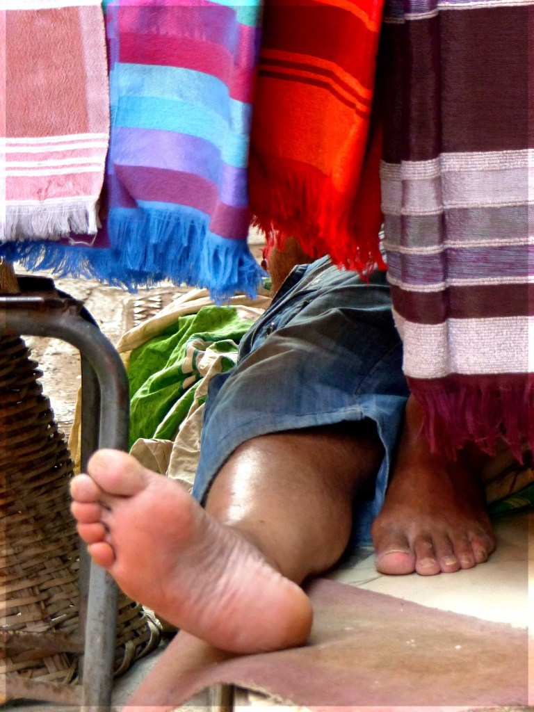 Bare feet sticking out from hanging textiles