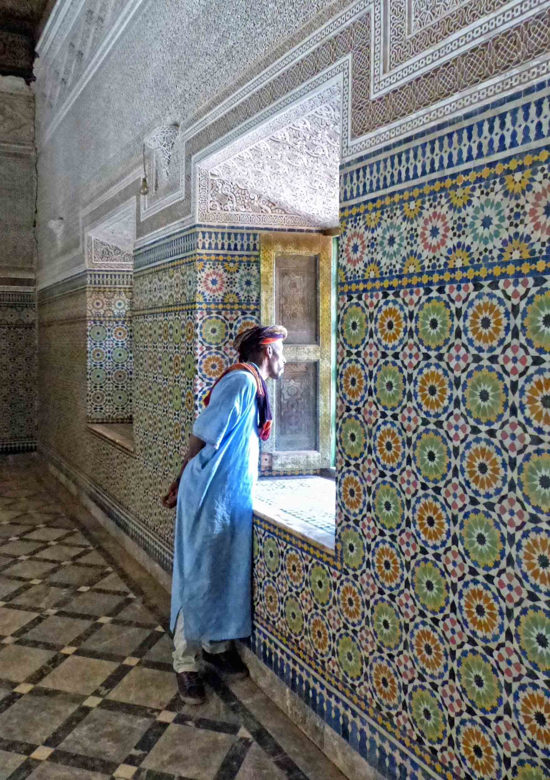 Man in blue robes looking out of window in tiled room