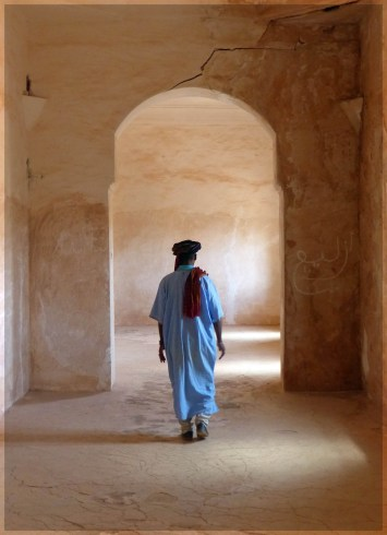 Man in blue robes walking through crumbling arches