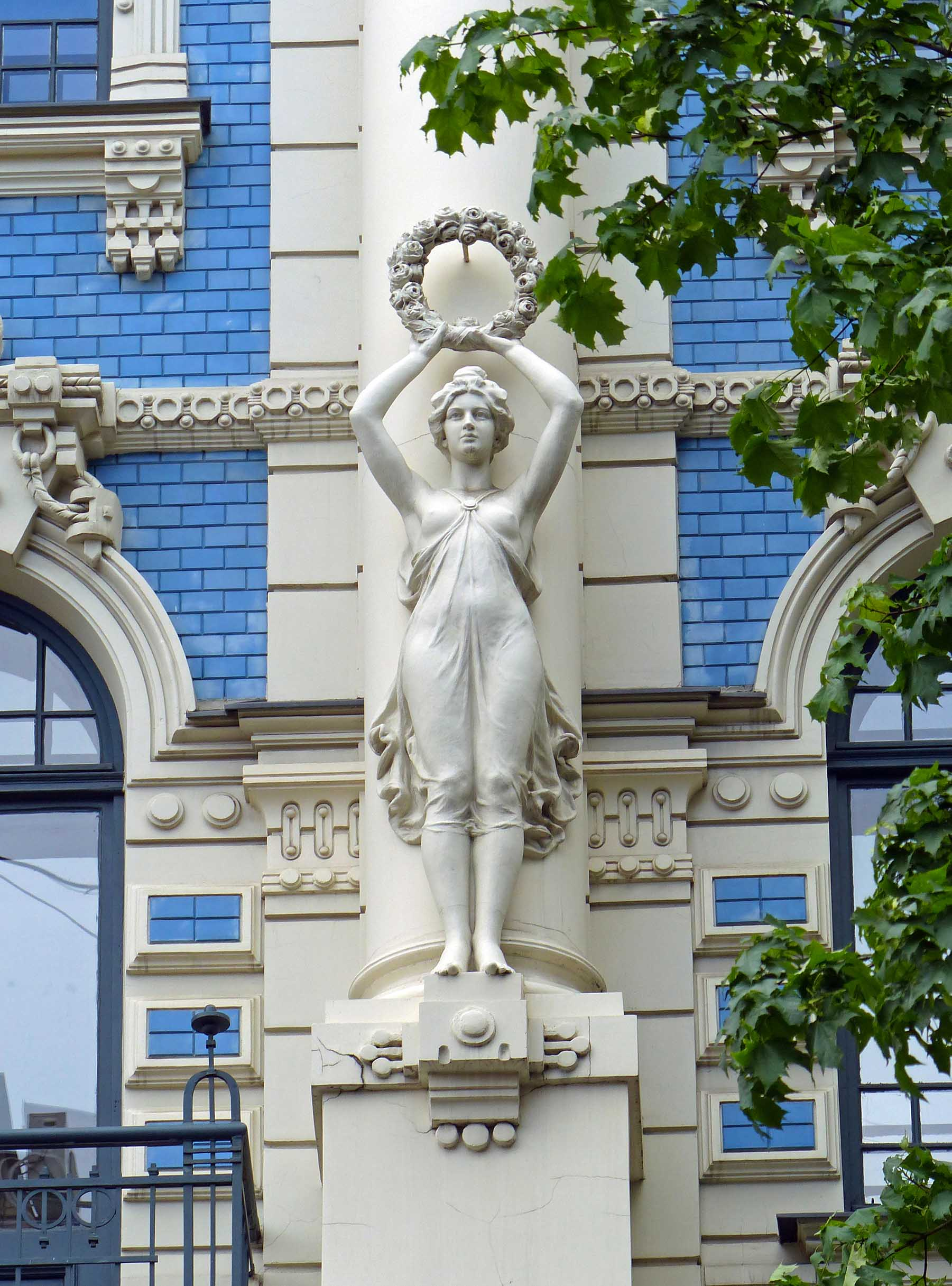 Stone female figure holding a wreath on the front of a blue building