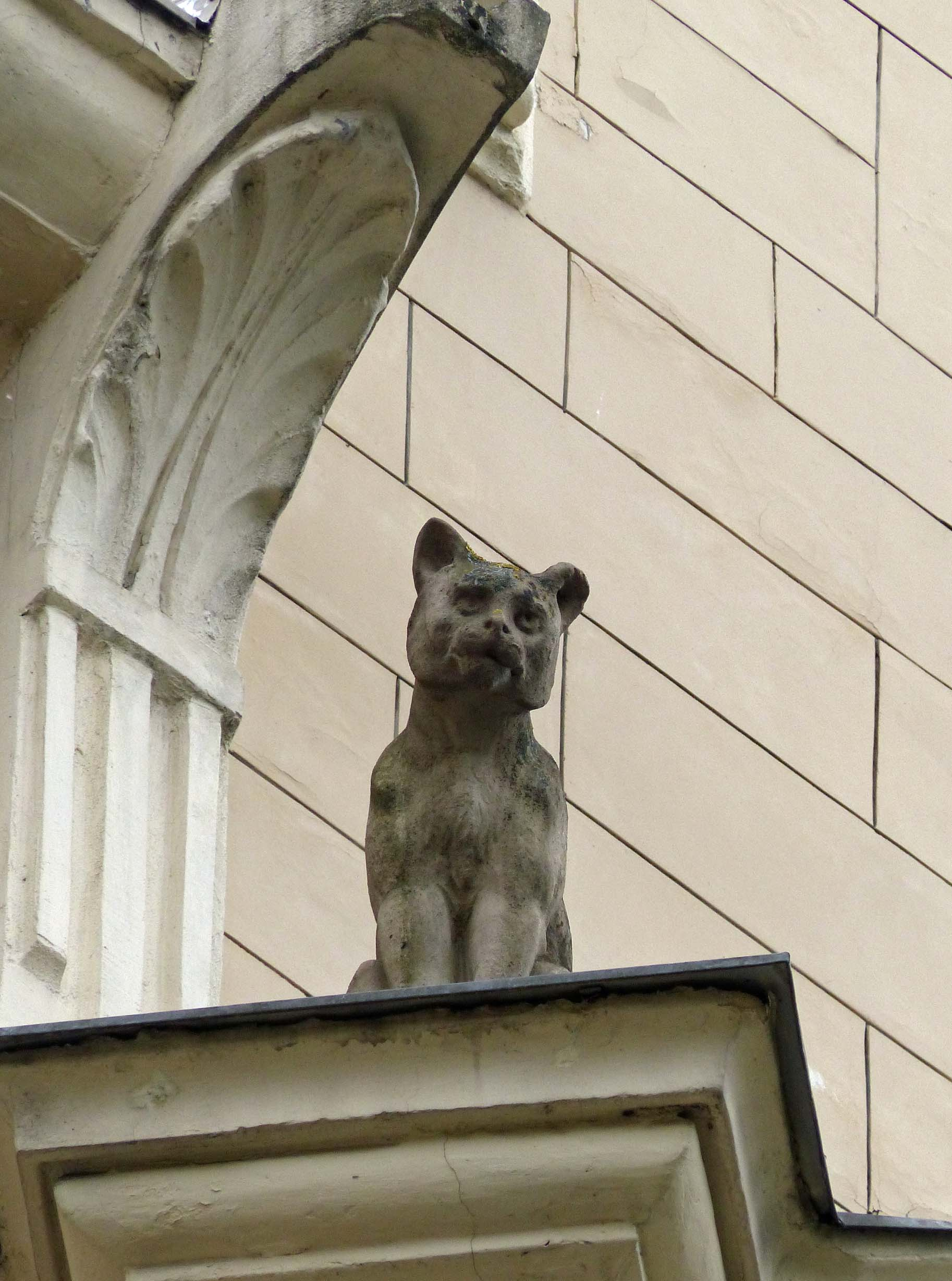 Small stone cat on a building ledge