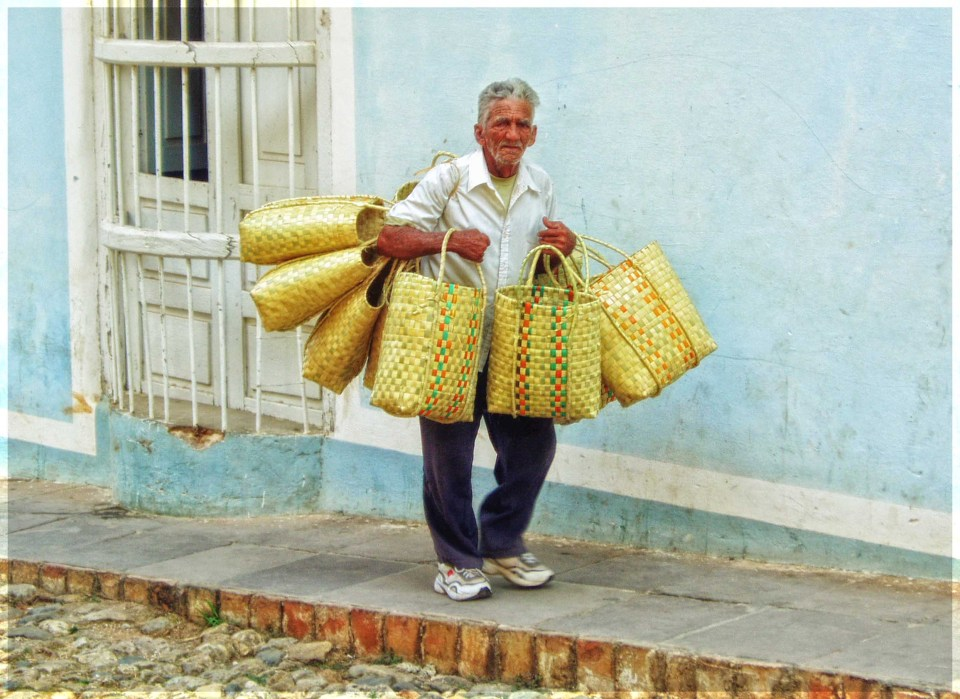 Man carrying a lot of straw baskets