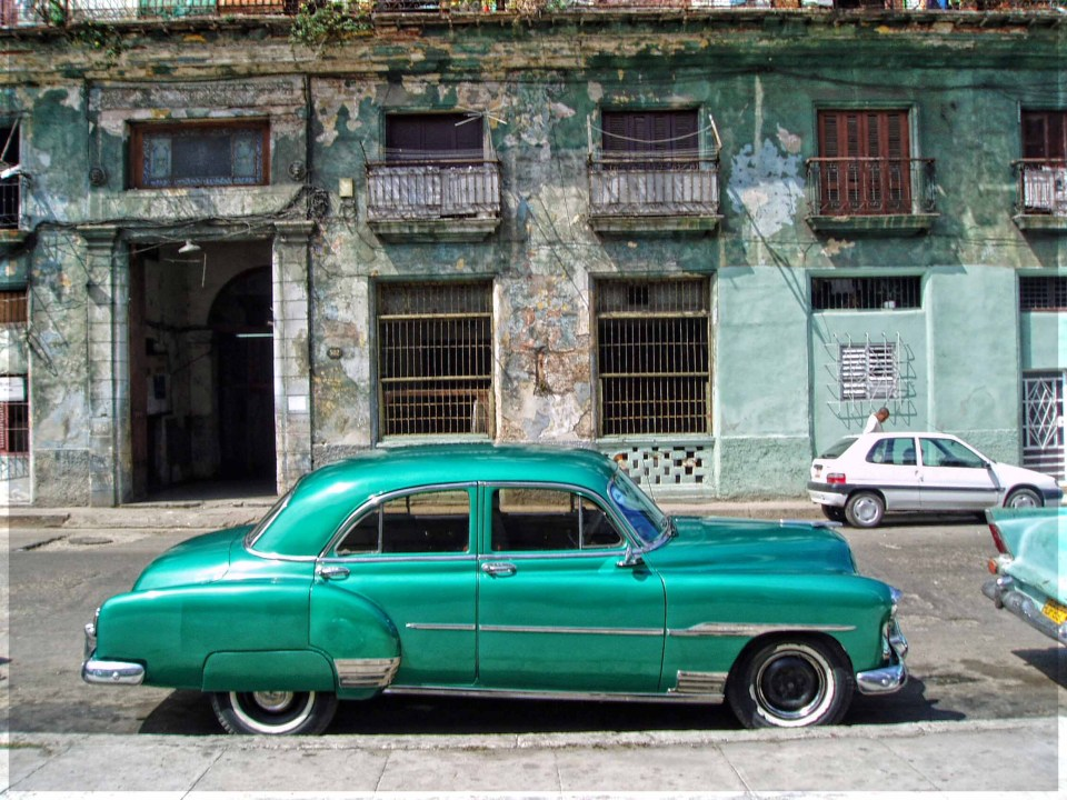 Old green car in front of dilapidated houses