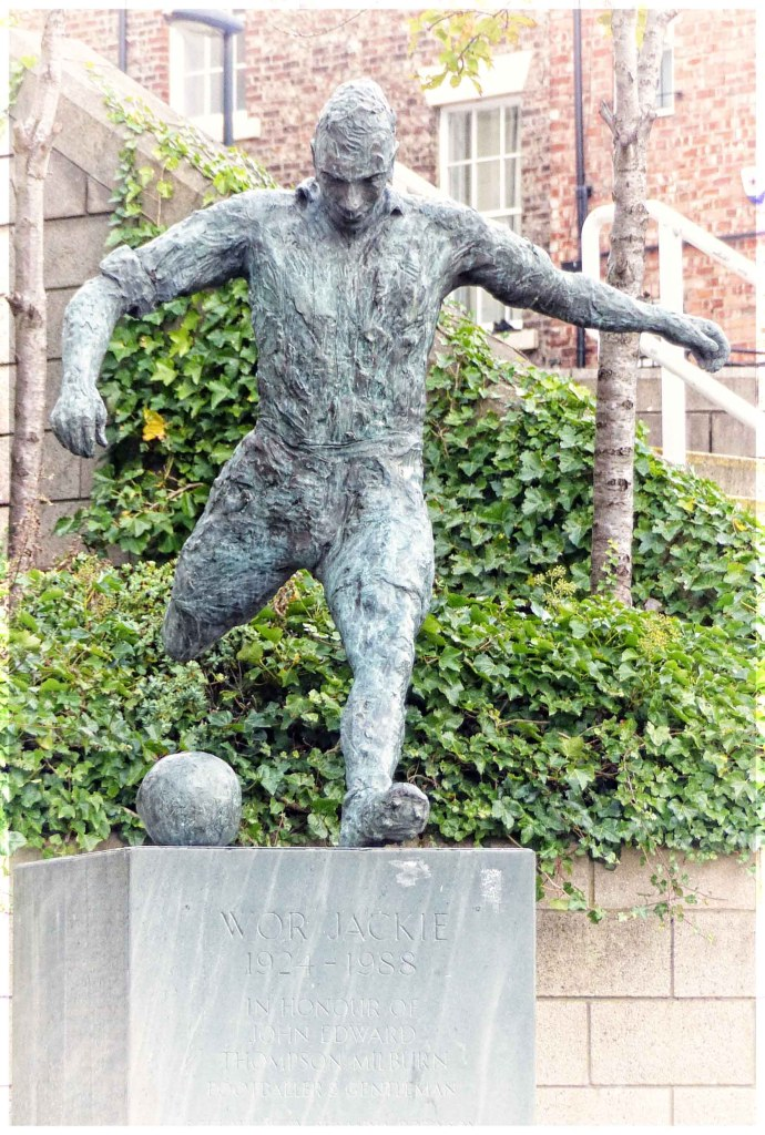 Statues of a footballer kicking a bal