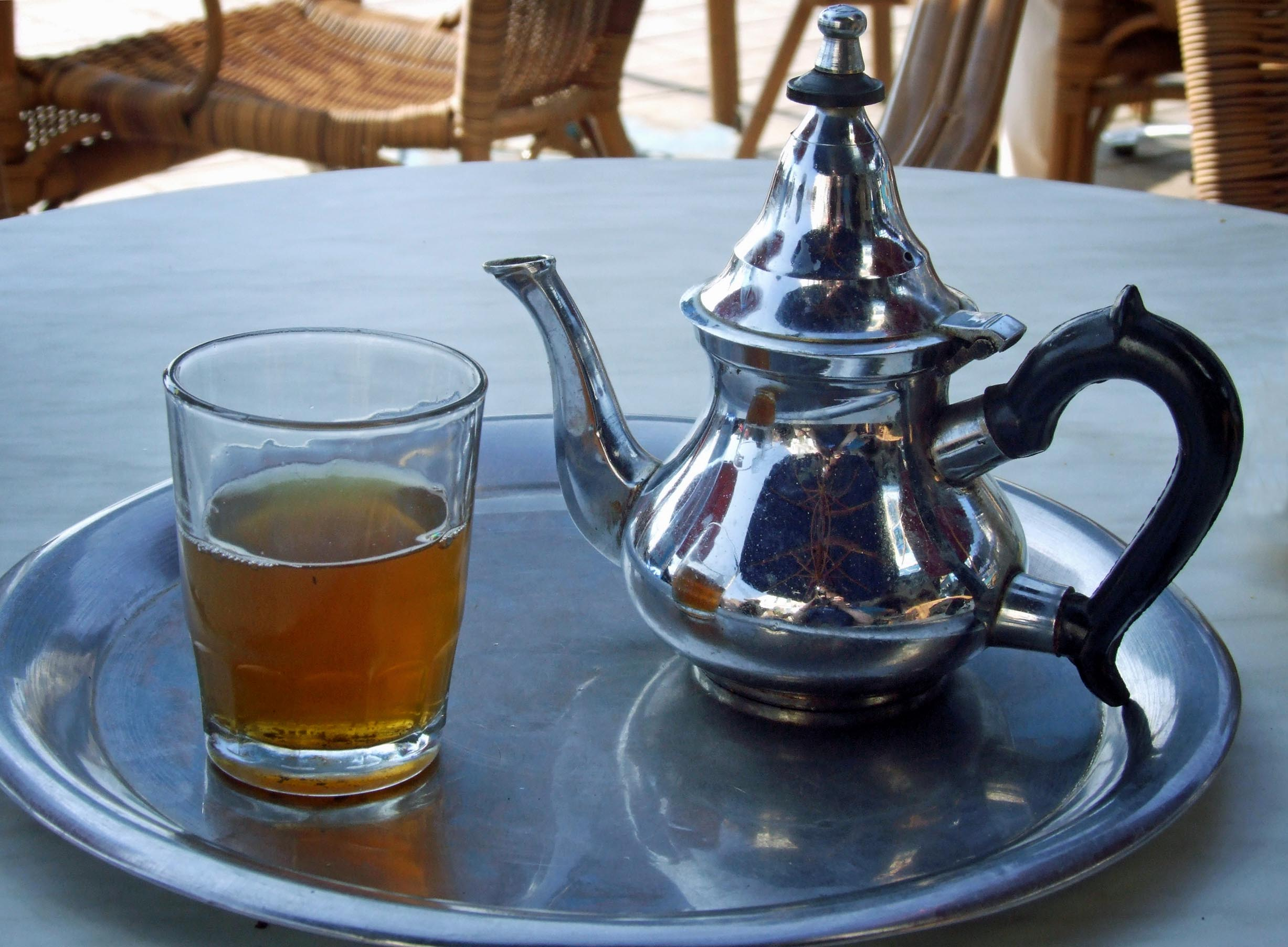 Tray with glass of tea and metal teapot